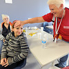 Pam Robinson, right, a registered nurse volunteer with the American Red Cross, checks on flood evacuee Julissa Garcia, 13, at the shelter in Loveland on Friday, September 13, 2013. Garcia was not feeling well. (Photo by Jenny Sparks/Loveland Reporter-Herald)