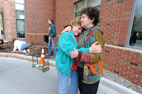 Cindy Sprague, left, and Euleta Palser embrace Thursday, October 24, 2013, outside the Loveland Public Library as others plant tulip bulbs in honor of Patty Goodwine, who died when her home was swept away by flood waters. Palser is Goodwine's sister and Sprague is a long time friend of Goodwine and worked with her for more than 30 years at the library. (Photo by Jenny Sparks/Loveland Reporter-Herald)