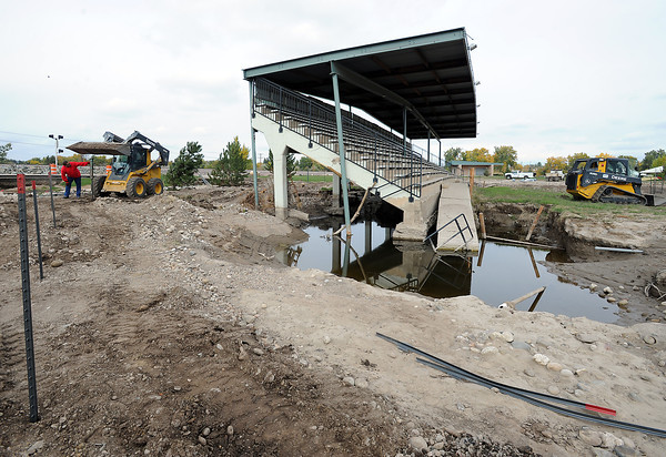 Nick Mishler, left, and Andrew Fierros, in the skid steer, City of Loveland Parks and Recreation employees, install a fence Thursday, October 17, 2013, around the flood damaged grandstands at Fairgrounds Park in Loveland. (Photo by Jenny Sparks/Loveland Reporter-Herald)