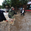18EPNews Flood 2 Helping Hands.jpg Volunteers help each other across fast-moving water on Elkhorn Ave. on Thursday evening. Residents got together to help sandbag businesses downtown and keep each other as safe as possible.