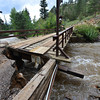15EP Flood Glacier Lodge Bridge.jpg A bridge over the Big Thopson River sits damaged and unusable on Saturday, isolating the Glacier Lodge. The bridge withstood years of spring runoff only to be nearly swept away by flood waters this week.