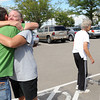 Robert Egloff, left, hugs Sharon Rady on Saturday, Sept. 14, 2013 at the Fort Collins/Loveland Municipal Airport where Sharon was picking up her mother Marge Rady, back, and father, not pictured, who were flown out of Drake where they were stranded by recent flooding.  (Photo by Steve Stoner/Loveland Reporter-Herald)