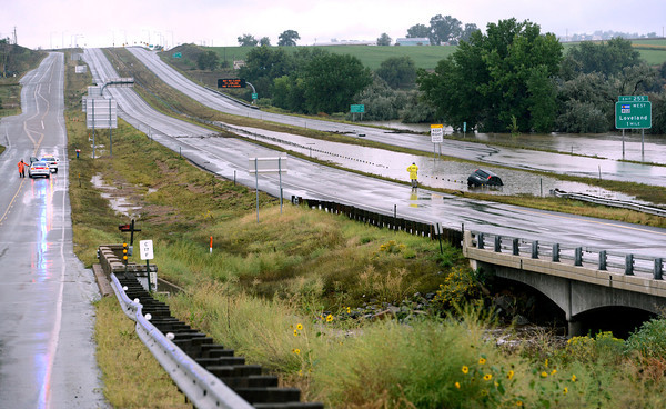 A car is submerged in water on a closed Interstate 25 south of Colorado 402 during flooding as emergency personnel block the frontage road on Friday, September 13, 2013. (Photo by Jenny Sparks/Loveland Reporter-Herald)