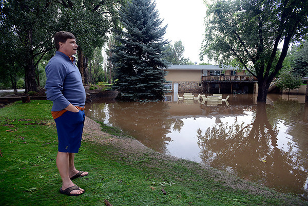 Peter Williams looks at his neighbor's home, which is standing in flood waters from the Big Thompson River on the 6700 block of Glade Road on Sunday, September 15, 2013 west of Loveland. (Photo by Jenny Sparks/Loveland Reporter-Herald)