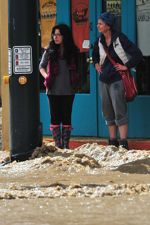 18EP Flood 2 Assessing.jpg Locals test to see how close they can get to their shops on Friday. Rising water from the Fall River divided parts of town, making travel dangerous or even impossible on Friday.