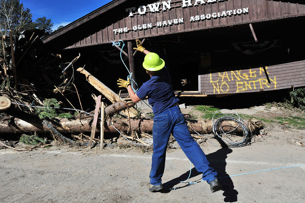 04EPGallery Glen Haven Return the power.jpg An Estes Park Light and Power worker flings a cable to a coworker in Glen Haven on Wednesday. Most of the inferstructure, as well as buildings, were destroyed in the flood.