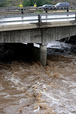 The Big Thompson River rages under an Interstate 25 bridge south of County Road 20E as Colorado State Patrol troopers block the road Friday, September 13, 2013. (Photo by Jenny Sparks/Loveland Reporter-Herald)