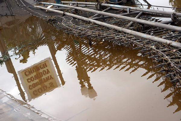A destroyed wrought iron fence at God's Country Cowboy Church is reflected in flood water in west Loveland on Sunday, September 15, 2013 west of Loveland. (Photo by Jenny Sparks/Loveland Reporter-Herald)