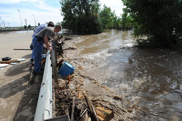 Stephen Strack checks out the debris and high running water in the Big Thompson River on Taft Avenue in Loveland on Friday, September 13, 2013. (Photo by Jenny Sparks/Loveland Reporter-Herald)