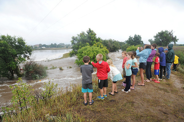 Youngsters watch for pumpkins floating past an area along the Big Thompson River just north of Mariana Butte Golf Course on Thursday afternoon after heavy rains caused flooding in Loveland, Colo. (Photo by Steve Stoner/Loveland Reporter-Herald)
