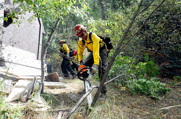 Pierre Blue Thunder, from Rosewood, North Dakota cuts away small trees from around a storage shed in the Fourmile Canyon fire in Boulder, Colorado September 9, 2010.  CAMERA/Mark Leffingwell (POOL)
