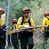 Fire fighters from Rosewood, North Dakota remove fire old wood and debris from around a home in the Fourmile Canyon fire area in Boulder, Colorado September 9, 2010.  CAMERA/Mark Leffingwell (POOL)
