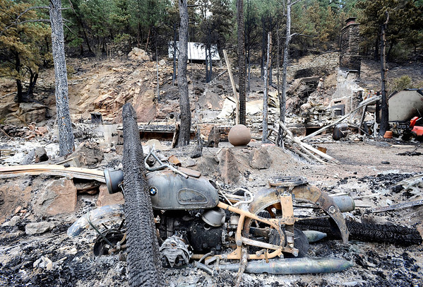 An old BMW motorcycle sits next to the road in front of a home that has been burned to the ground near the Wallstreet are of the Fourmile Canyon fire in Boulder, Colorado September 9, 2010.  CAMERA/Mark Leffingwell (POOL)