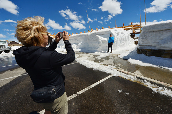 A couple take photos in front of the snow-covered Alpine Visitor Center on Friday. Rocky Mountain National Park road crews got the Trail Ridge Road open on Friday, by still has work to do to get the visitor center and Trail Ridge Store open for the season.