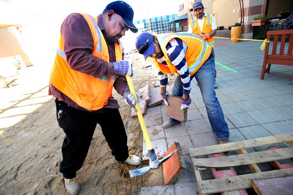 "Arturo Teller, left pries up a paving stone while Eliseo Ramirez loads them onto a pallet at the Twenty Ninth Street Mall in Boulder Colorado on Wednesday. The crew was working on the beginning stages of an ice and roller skating rink that will be in the heart of the mall. Efrain Aguilar looks on from the background. <br /> For more photos from the mall go to  <a href=""http://www.dailycamera.com"">http://www.dailycamera.com</a>.<br /> Photo by Paul Aiken / October 12, 2001"