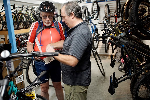 BEN GARVER — THE BERKSHIRE EAGLE<br /> Salesperson Erik Forestell (right) talks with Peter Strauss in the bicycle section of the Arcadian Shop in Lenox, Wednesday, August 14, 2019. Outdoor gear other than clothing will be covered over the tax free weekend.
