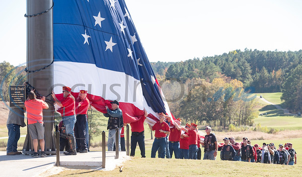 """Veterans from the Longview Marine Corps League hold up the American flag during the flag raising ceremony at Tempest Golf Club in Gladewater on Veterans Day, Wednesday, Nov. 11, 2020. The golf course's new monument, a 208 foot tall flagpole called """"We the People"""" flies a large flag 90 by 180 feet wide."""