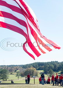 """Veterans from the Longview Marine Corps League keep the flag from touching the ground as it is raised up a 208 foot tall flagpole during the flag raising ceremony at Tempest Golf Club in Gladewater on Veterans Day, Wednesday, Nov. 11, 2020. The golf course's new monument, a 208 foot tall flagpole called """"We the People"""" flies a large flag 90 by 180 feet wide."""