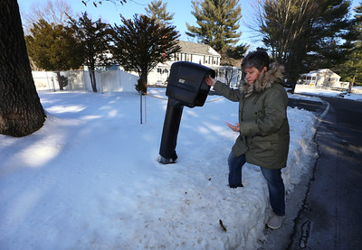 Doreen Majeau of Chelmsford, at the group home where her son Michael, 29, who has autism, lives. After complaints by the next door neighbor, the group home closed its driveway on that side (under the snow under yellow chain), and extended a second driveway and made other changes to how residents enter the house. She's checking for mail. The mailbox is still by the closed driveway. (SUN/Julia Malakie)