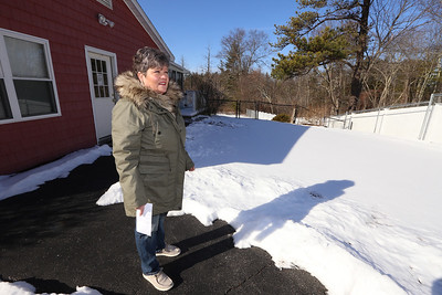 Doreen Majeau of Chelmsford, at the group home where her son Michael, 29, who has autism, lives. After complaints by the next door neighbor, the group home closed its driveway on that side (under snow), and no longer use the entrance door behind her. The neighbors put up the fence at right. (SUN/Julia Malakie)