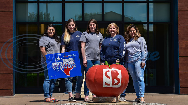 Jacksonville Southside Bank employees (from left to right) Odette Rivero, Jordan Curtis, Molly Loughmiller, Kathy Hardy and Alejandra Wright smile for a photo while standing next to a Texas Strong, Pray Together sign on Wednesday, April 15. The signs were made and distributed free of charge by iSignShop to bring hope amid the hardships caused by the Coronavirus pandemic.