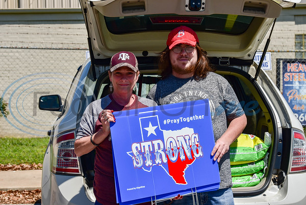 Jacksonville residents Melody Walters (left) and Anthony Walters (right) pick up Texas Strong, Pray Together signs from iSignShop on Wednesday, April 15. The company is distributing the signs free of charge to promote hope and solidarity in the community during the Coronavirus pandemic.