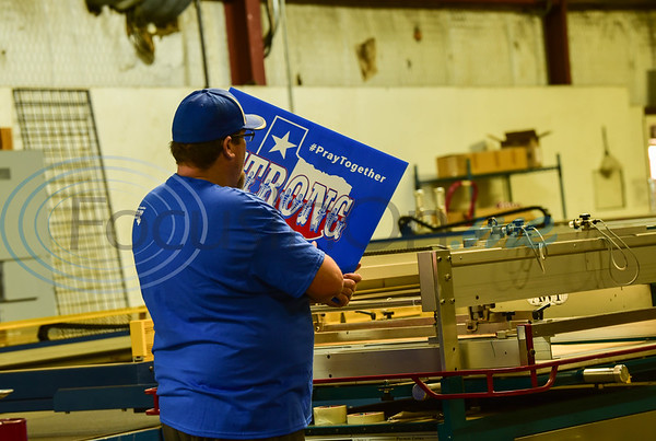 iSignShop Shop Manager Paul Fite inspects a Texas Strong, Pray Together sign the company is making and distributing free of charge to local businesses and residents in the wake of the Coronavirus pandemic.