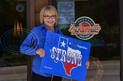 Jacksonville Chamber of Commerce President Peggy Renfro holds a Texas Strong, Pray Together sign by iSignShop on Wednesday, April 15. The sign company distributed the signs free of charge as a way to bring hope and solidarity to the community.