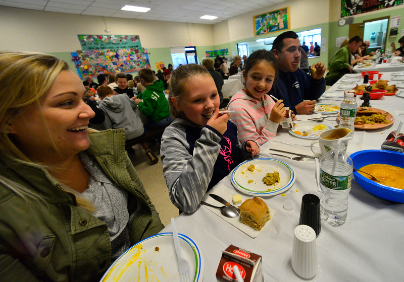 KRISTOPHER RADDER — BRATTLEBORO REFORMER<br /> Sofia Dow, 10, takes a bite of food as members of her family look on during the annual Thanksgiving luncheon at Vernon Elementary School on Thursday, Nov. 15, 2018.