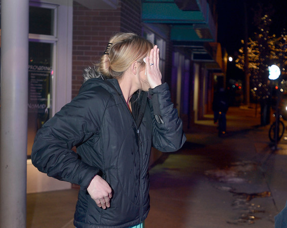 An unidentified woman tries to clean some sort of pepper spray from her eyes next to The Dandelion Dispensary while police investigating an alleged robbery on Thursday, Jan. 3, in Boulder. The suspects fleed the scene and allegedly used some sort of pepper spray while robbing the business<br /> Jeremy Papasso/ Camera