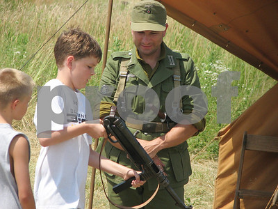From right, re-enactment participant Karl Allison, of Akron, supervises while 10-year-olds Zac Miller and John Janowski, both of Brunswick, examine a World War II weapon as part of a battle re-enactment at Heritage Farm in Brunswick on Sunday, July 18, 2010.