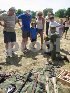 Re-enactment participant Karl Allison (kneeling), of Akron, demonstrates the intricacies of a particular World War II weapon during a battle re-enactment event in Brunswick on Sunday, July 18, 2010.