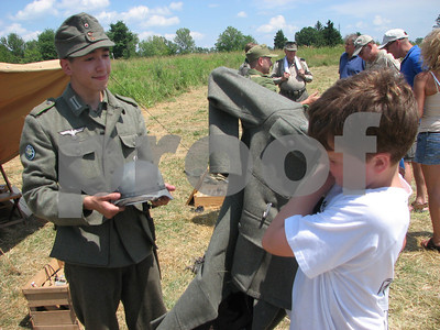 Re-enactment participant Alex Lawson, 17, of Pickerington, assists 10-year-old Zac Miller, of Brunswick, as he dons a German World War II outfit as part of a battle re-enactment event at Heritage Park on Sunday, July 18, 2010, in Brunswick.