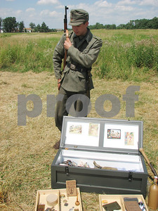 Re-enactment participant Alex Lawson, 17, of Pickerington, showcases his German World War II collectibles. All the items belonged to participants in the battle re-enactment event at Heritage Farm in Brunswick on Sunday, July 18, 2010.