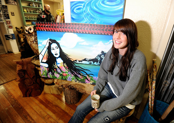 Artist Kyrie Wozab, of Louisville, sits next to her painting while hanging out on Wednesday, Jan. 2, at The Hive Co-Op Cannabis Club in Lafayette.<br /> Jeremy Papasso/ Camera