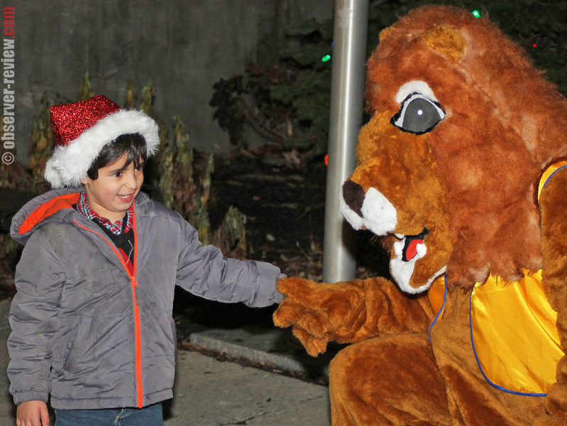 Ronan Mircandani is greeted by the Lion's Club's Leo the Lion after the lighting of the Lion's Club tree.