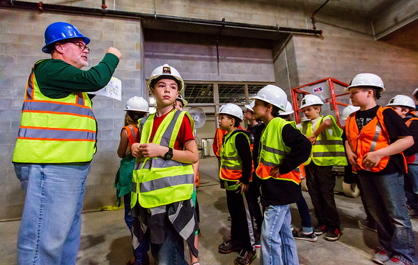 JAY YOUNG | THE GOSHEN NEWS Syracuse Elementary third-grade student Brock Gest watches construction workers while Wawasee Community Schools superintendent Tom Edington points to a map showing the group where they are during a tour of the new elementary school that is still under construction on Thursday morning.