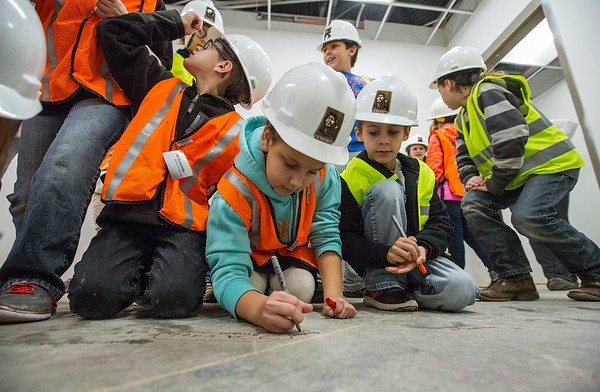 JAY YOUNG | THE GOSHEN NEWS Syracuse Elementary third-grade student Sophia Smith signs her name on a concrete slab it what will become the principal's office during a tour of the new elementary school that is still under construction on Thursday morning.