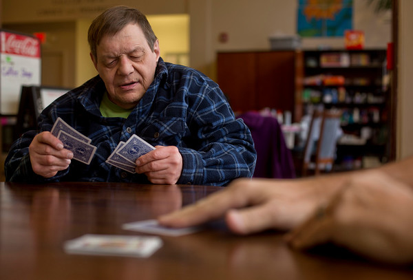JAY YOUNG | THE GOSHEN NEWS Joe Lehman checks the cards in his hand while waiting for his turn during a weekly Euchre game Wednesday morning at Gaining Grounds.  Lehman has been playing since 2008, when his family moved away and he needed a new group to play with.