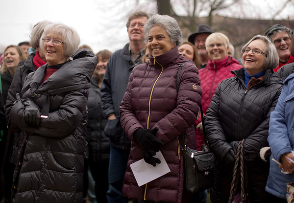 JAY YOUNG | THE GOSHEN NEWS Annie Mathew, center, of Goshen, smiles as she and others attend a prayer gathering on the lawn of the Elkhart County Courthouse in downtown Goshen on Friday afternoon. The event, which was organized by Elkhart County HOPE (Helping Our People Everywhere), was scheduled to coincide exactly with the time that Donald J. Trump was sworn in as the nation's 45th president. At the event, members of the community offered prayers and songs aimed at bringing everyone together and offering hope for all.