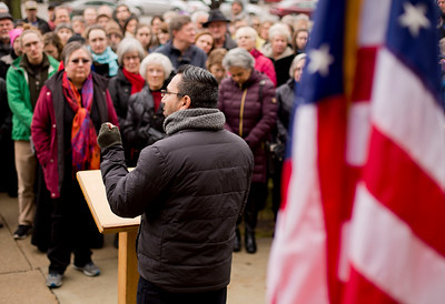JAY YOUNG | THE GOSHEN NEWS Attendees gather around as Saulo Padilla of the Mennonite Central Committee speaks during a prayer gathering on the lawn of the Elkhart County Courthouse in downtown Goshen on Friday afternoon. The event, which was organized by Elkhart County HOPE (Helping Our People Everywhere), was scheduled to coincide exactly with the time that Donald J. Trump was sworn in as the nation's 45th president. At the event, members of the community offered prayers and songs aimed at bringing everyone together and offering hope for all.