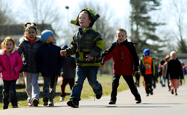 JAY YOUNG | THE GOSHEN NEWS West Noble Elementary kindergarteners Bentley Mahon, left, and Christian Castro run down the track during recess Wednesday afternoon in Ligonier. Students at the school walk laps every day as part of a fitness program. To date, they have walked 26,289 miles total.