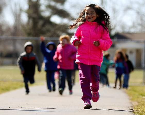 JAY YOUNG | THE GOSHEN NEWS West Noble Elementary kindergartener Karen Calderon runs ahead of a group of students as they walk laps around the track during recess Wednesday afternoon in Ligonier. Students at the school walk laps every day as part of a fitness program. To date, they have walked 26,289 miles total.