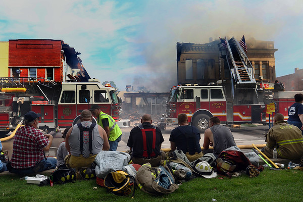 JAY YOUNG | THE GOSHEN NEWS<br /> Firefighters take a rest after helping to battle a large fire in downtown LaGrange Tuesday afternoon.