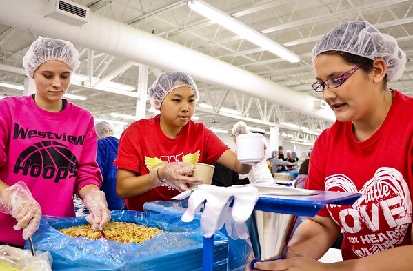 LEANDRA BEABOUT | THE GOSHEN NEWS<br /> Westview seniors measure out dehydrated vegetables for Feed My Starving Children's MannaPacks. From left: Chloe Lovell, Sabrina Yun and Alyssa Hart.