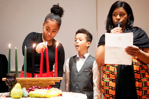 BEN GARVER — THE BERKSHIRE EAGLE<br /> Spencer Reed watches his sister Shanyse Yasmine Reed light candles for Kwanzaa while their mother Leah Redd narrates at The Women of Color Giving Circle of the Berkshires annual Kwanzaa Celebration at the Whitney Center for the Arts in Pittsfield, Friday December 28, 2018.