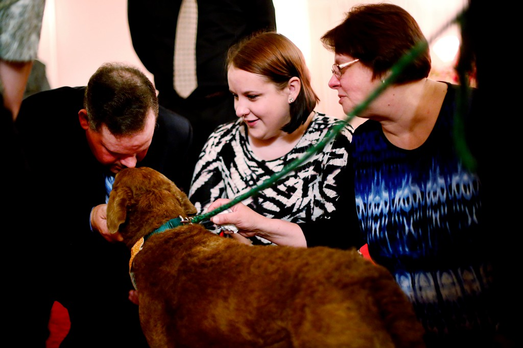 . Tom, left, Meaghan, center, and Marie VanBramer find solace in Greyce, a 2-year-old Chesapeake Bay retriever, at the wake of their mother, grandmother, and mother-in law, respectively, at Dwyer Funeral Home in Pittsfield. Greyce and her handler Jody Tierney visit the funeral home for free to provide an element of extra support for grieving family and friends of the deceased. Friday, October 21, 2016. Stephanie Zollshan � The Berkshire Eagle | photos.berkshireeagle.com