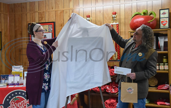 Tomato Fest t-shirt design winner Heather Harris (left) and Tomato Fest Chairman Robin Butt prepare to reveal Harris' design on Thursday, February 20. Harris won $200 and the first Tomato Fest t-shirt with her design.