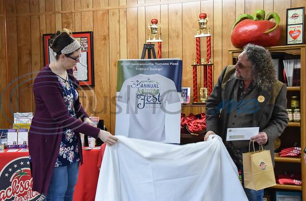 Tomato Fest t-shirt design winner Heather Harris (left) and Tomato Fest Chairman Robin Butt reveal Harris' design on Thursday, February 20. Harris won $200 and the first Tomato Fest t-shirt with her design.