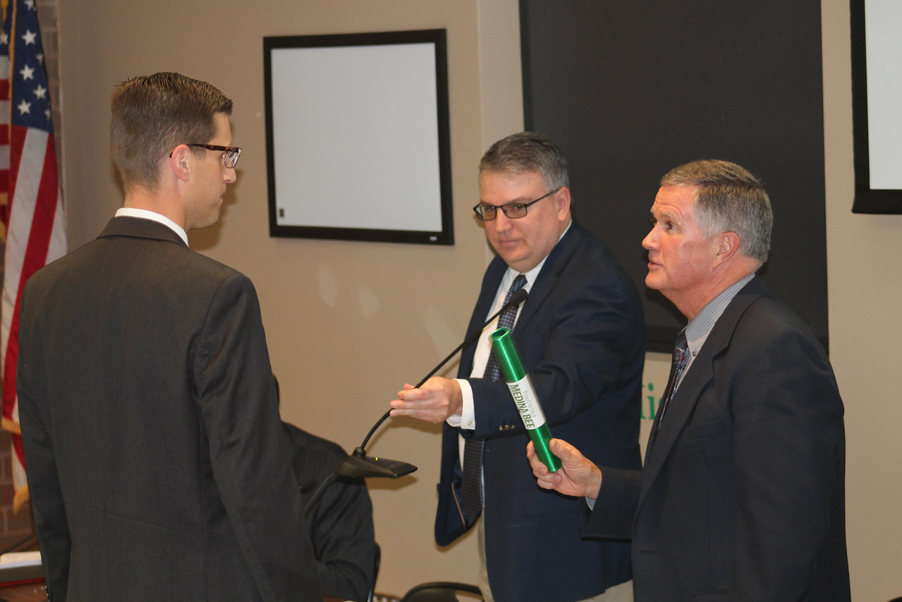 LAWRENCE PANTAGES / GAZETTE Retiring Medina City Schools Superintendent Dave Knight (right) discusses a ceremonial passing of a green torch to incoming Superintendent Aaron Sable on Monday night during a Medina Board of Education meeting. Holding a microphone for Knight is board president Rob Skidmore.